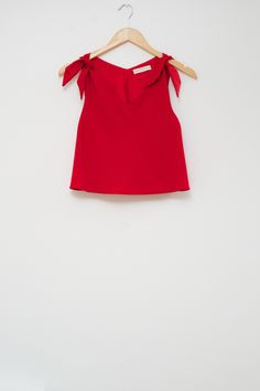 This crop top is made from the softest British woven wool crepe, with a silk lining. It is cut on the bias, with shoulder tie bows. It can be paired with the Oak Skirt as a two-piece ensemble outfit.  Pictured here in red.