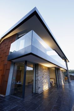 sliding minimal windows and fixed structural elements provide a frameless glass front to this contemporary new build www.iqglassuk.com
