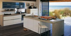 White Kitchen Island With Grey Solid Surface Countertops And White Bar Stools Above Hardwood Flooring