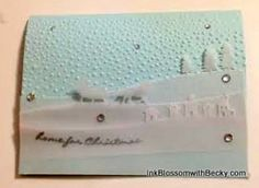 2015   Sleigh Ride edgelets, vellum paper, Soft Sky cardstock and the Softly Falling embossing folder.  After the card parts were cut we embossed the Home for Christmas sentiment in Silver embossing powder.