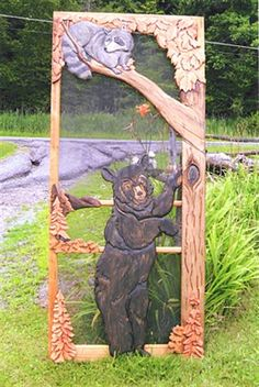 Carved wood screen door with bear, raccoon and tree
