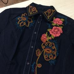 Embroidered western style Top This top is fabulous!!! Beautiful floral  embroidery on both the back and front.  Dark blue pearl snap front.  Nice top stitching outlines the tailored cut on this beauty.  More embroidery at the French open cut sleeves. A crown is stitched  in a rose gold  on the back with  more embroidered flowers. It's finished with  a printed  waterfall like detail down the back.  This top has some stretch so it's  got a lovely fit as well.  Size Medium Love Polly Tops…