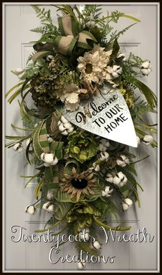"Floral swag in greenery, florals and cotton bolls and accented with a galvanized ""Welcome Home"" sign by Twentycoats Wreath Creations (2017)"
