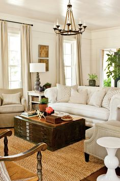 Start at the top. A chandelier gives the living room a visual center.    Use the full range of neutrals. From white fabric to dark wood, a neutral room is made more interesting when you mix various tones.  Choose a statement sofa for a large room. A tufted chesterfield sofa covered in family-friendly Sunbrella fabric adds scale and traditional style. Tip: A large sofa needs large pillows—ours are 26 inches square.  Editor's Tip: Reinvent vintage finds in a new setting. Here, an old flat…