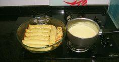 Massa:  - 1 copo de leite (250 ml)  - 1 ovo inteiro  - 3 colheres (sopa) cheias de farinha de trigo  - 1 dente de alho  - 1 sazón amarelo  - Sal a gosto  - Recheio:  - Presunto (150 g)  - Queijo mussarela (150 g)  - Molho branco:  - 2 colheres (sopa) de margarina  - 1 copo de leite (250 ml)  - 1 1/2 colher (sopa) de farinha de trigo  - 1/2 sazón amarelo  - sal a gosto  -