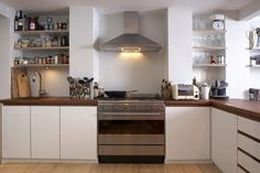Handle-less kitchen, walnut trim recesses, walnut worktop. Like the look, but would prefer handles.
