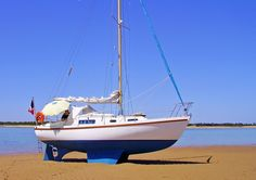A Macwester 27 sailboat, sitting perfectly on her bilge keels and skeg-hung rudder on a beautiful sandy beach.