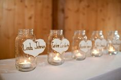 in memory of, rustic hearts from braggingbags on etsy that I hung on mason jars with candles.  each person is someone in our families who have passed or are not able to make it to the wedding