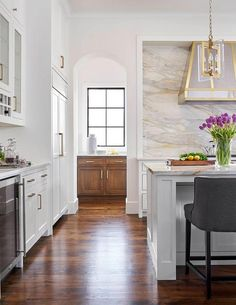 Elegant white kitchen with a stove nook features a gray and gold marble cooktop backsplash and a stainless steel and brass range hood.