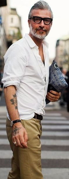 Simple casual wear. And hes even holding his womans bag for her. A true cool gentlemen. Love the tats too!