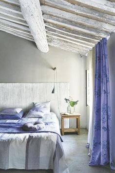 Azul, gris, blanco...  Este trío es todo un acierto si quieres un dormitorio fresco y relajante. Aquí se combinan en las cortinas, la ropa de cama y la colcha de lino, de Designers Guild. Las vigas del techo se pintaron en blanco.  Un panel de madera pintada en blanco forma un cabecero rústico.  Cortinas y visillos en azul y blanco, respectivamente, visten la ventana.