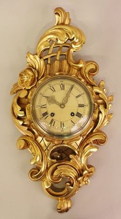 """A Gilt Wood Exacta Wall Clock. Circular lock face with """"Exacta Sweden"""" and roman numeral numbers on cream. Surrounded by scrolled foliates, floral and lattice work decoration."""
