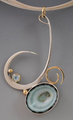 """green limpet from the Pacific Coast of Mexico sr=et is sterling silver and 14kt gold with blue topaz. On a 16"""" multi strand sterling cable collar."""