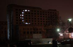 Morfai  è il nome d'arte di uno street artist di 29 anni che vive a Kaunas (Lituania). Per il suo ultimo progetto ha comprato dei fogli di polietilene, del nastro adesivo e ha scelto di dar luce a un grande edificio abbandonato della sua città. Ha misurato le finestre della struttura e