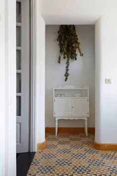 an armful of leaf laden branches gathered like herbs to dry and hang above a small cabinet.