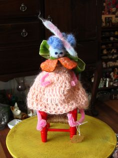 small doll made with pipe cleaners with knitted dresss