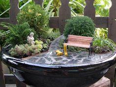 pot de fleurs original en céramique à vernis noir, plantes vertes, buis taillés, banc et allée décoratifs