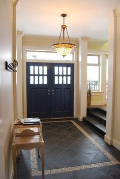 This foyer acts as the main hub of the home as all rooms branch off from here. Stairs lead to the dining and kitchen areas as well as the living and family rooms. The stone tiles define the space with an inlay river rock border. The long window that runs above the width of the doors lets in additional light and adds height to this main point of entry.