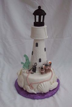 light house cake - gumpaste, pearl luster dusted seashells.  Gumpaste lighthouse formed over styrofoam cone.  Then I made a cone about same size out of rice krispies treats and placed the dried gumpaste cone shell over the rice krispy treat cone.  I frosted the rice krispy cone with some royal icing to get best fit.  Did this for structural stability of lighthouse.  Seagulls on logs.