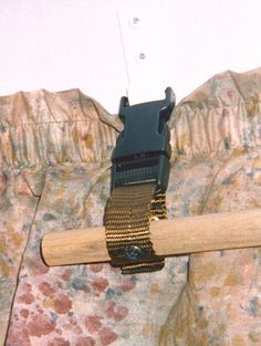 """Detail showing one of the very short webbing belts; just a few inches of 1"""" webbing riveted onto a male buckle end and screwed to the rod.  The rod never comes down; the last word in deployment/stowage."""
