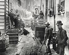 Fotografia de uma das ruas da favela de Five Points, em Nova York, por Jacob Riis (ca 1890).