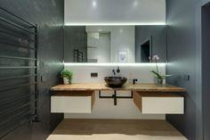 Cerâmica hexagonal, padrão em alta, compõe o banheiro, com gaveteiros suspensos e espelho com iluminação.