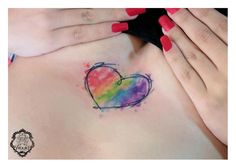 marvelous rainbow heart watercolor tattoo on chest for girls