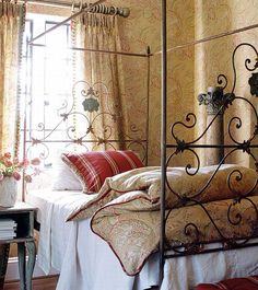 Beautiful French style bedroom with a curved steel framed bed. The wallpaper, the curtain and bed linen has the same pattern to pull the look together. Oh, I loooove this!