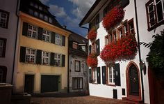 A very beautiful architectural/floral street scene in Basel, Switzerland- the sunlit white building & the profusion of red flowers in the window boxes are extremely attractive!! Superb imagery!!