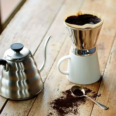 A single-serving, manual coffee brewing system by Melitta featuring a hi-shine brewer and white mug.