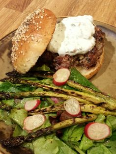 Lamb burger with feta, mint, za'atar and tzatiki sauce on freshly baked potato roll; grilled asparagus; spring mix with balsamic vinaigrette.