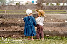 little boy and girl stand next to a fence