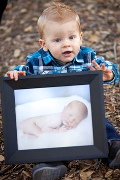 1 year photo, holding his newborn photo- T's is coming... @Marie Jones want to come do this shot!! I have to have it!