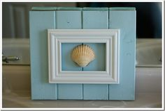 White shell in white frame with turquoise wall showing through. Can maybe use glass as mat and glue the shell to it.