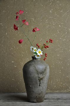 White daisy, red berries and red autumn  leaves on a branch ikebana