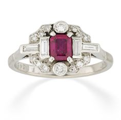 A ruby and diamond tablet ring, the central ruby weighing approximately 0.5 carats, surrounded by twelve eight-cut, two brilliant-cut and four baguette-cut diamonds, mounted in platinum and 18ct white gold, circa 1930.
