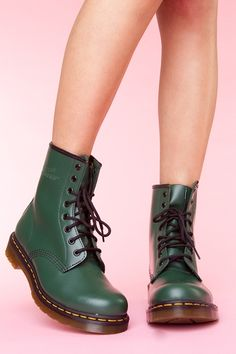 The iconic lace-up combat boot in smooth green leather featuring contrast stitching and a stitched logo bootstrap at back. Gum rubber sole, low stacked heel. Fully lined. Looks awesome paired with a vintage tee and skinnies! By Dr. Martens.