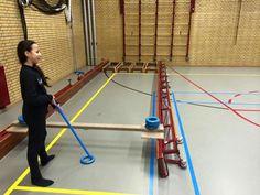 Sjoelen in de gymzaal met stok en plastic ringen. Sjoelbak opsluiten d.m.v. omgekeerde banken. Kastbovenstukken vormen het scorevak van de sjoelbak.