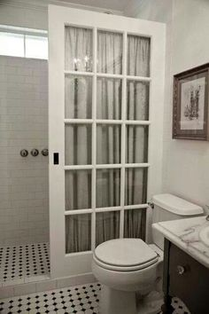 Use an old French pocket door instead of an expensive glass shower enclosure
