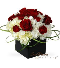 I like how the lily grass is wrapped back in. White hydrangea, red roses, red spray roses and lily grass.
