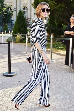 Olivia Palermo wears a striped button-down top, striped trousers, sandals, and Dior sunglasses