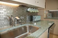 Recycled glass countertops - Vetrazzo. Also the mugs hanging under the cabinets is neat, must do!