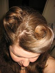 Victory rolls are swept up away from the face, rolled and pinned toward the top of the head.