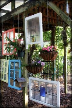 Leaded glass and old stained glass windows mixed with hanging flower pots...what a clever visual divider for a garden space.