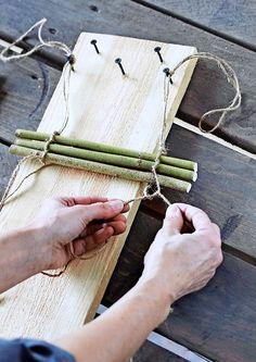Tee leveähköstä laudasta sidontapuu. Ruuvaa lautaan neljä ruuvia erilevyisten pajumattojen tekoa varten. Kiinnitä yhteensolmitut narut kahteen ruuviin. Tee naruihin solmut, laita pajutikku narujen väliin ja solmi narut tiukasti tikkujen ympärille.