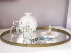 Simple, elegant accessories on a mirrored tray add to the feminine style of this lavender bedroom.