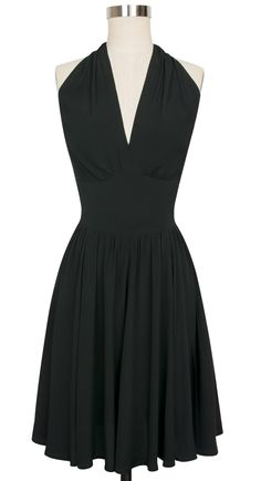Our retro signature halter style, the Dottie Dress, is here in black rayon crepe de chine. This version of the Dottie Dress features a knee-length gathered skirt with pockets. The design features a lightly gathered bust that crosses over in the front with a high pointed under bust. The wide halter style straps tie at the back of the neck for added support. With elastic ruching at the sides, the bodice of the Dottie molds to your form. #trashydivadottiedress #trashydivalbd