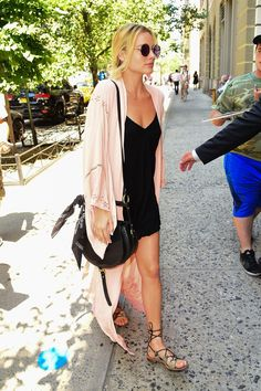 Margot Robbie in a blush pink kimono by Spell & The Gypsy Collective, mini-slip dress, John Lennon-esque sunglasses, hobo bag and python-trimmed gladiator sandals.