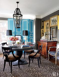 In the dining room of this Kansas City, Missouri, home, the pedestal table is by Restoration Hardware, the folding screen is vintage, and the drawings are by S. Holinko.