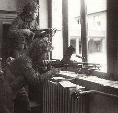 A Canadian soldier with a Bren submachine gun in a house in the suburb of Vaucelles